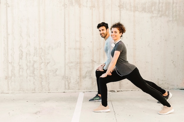 Cheerful man and woman lunging together