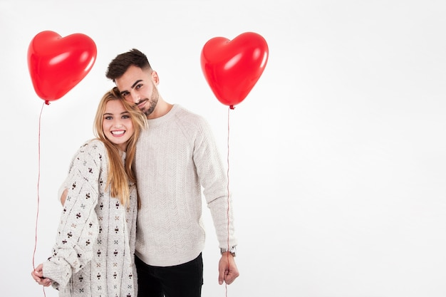 Cheerful man and woman posing with balloons