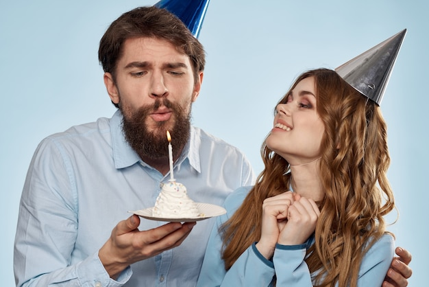 Cheerful man and woman with cake in a plate corporate party blue background