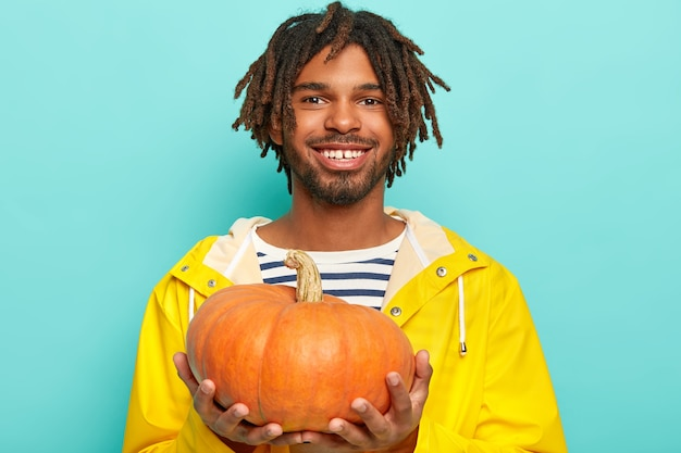 Cheerful man in yellow raincoat boasts his autumn crop, holds pumkin, smiles pleasantly, poses over blue wall