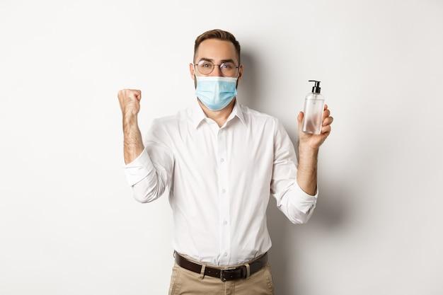 Веселый менеджер в медицинской маске, показывающий дезинфицирующее средство для рук, стоя