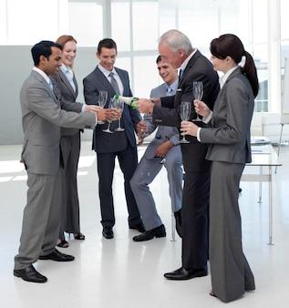彼のチームにシャンパンを提供する陽気なマネージャー