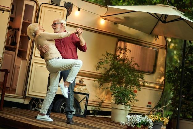Cheerful married couple enjoying dance outdoors near their motorhome
