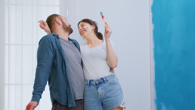 家のリフォーム中に楽しんでいる陽気な夫婦。改装と改善中のアパートの改装と住宅建設。修理と装飾。