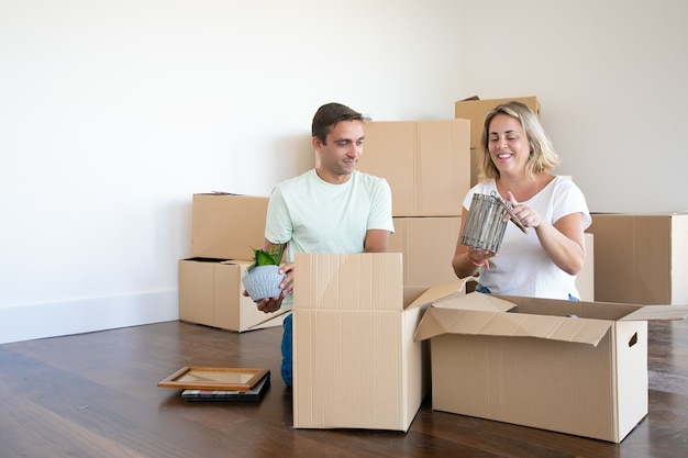 Cheerful married couple moving into new apartment, unpacking things, sitting on floor and taking objects from open boxes