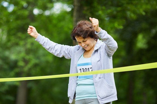 最初にマラソンレースを終える茶色の髪の陽気な成熟した大人の女性、ミディアムポートレート、コピースペース