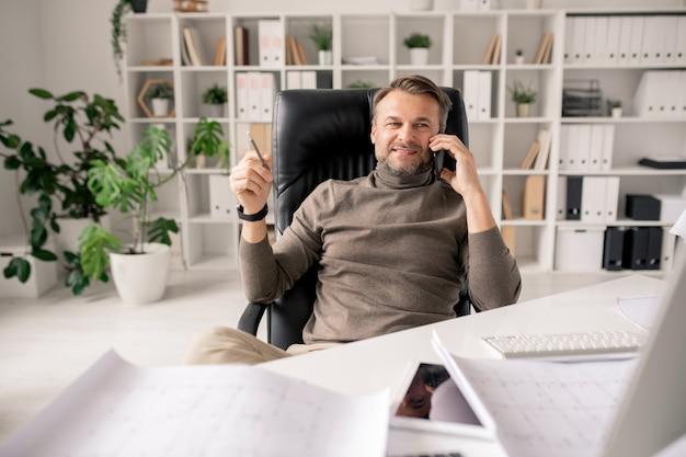 陽気な成熟した建築家またはオフィスに座っている間クライアントまたは同僚の1つと話しているスマートフォンを持ったビジネスマン