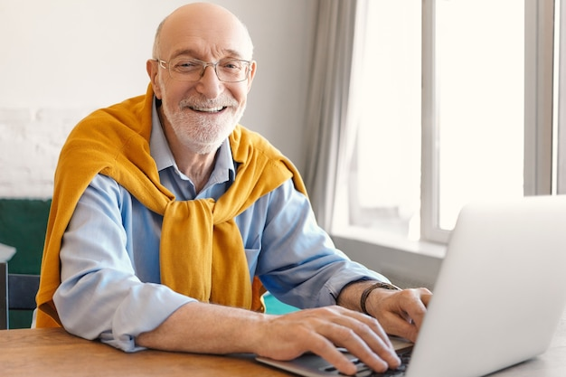 Веселый зрелый бородатый лысый мужчина-предприниматель в очках и свитере поверх синей формальной рубашки счастливо улыбается, играя на клавиатуре на портативном компьютере, играя в видеоигры во время обеденного перерыва