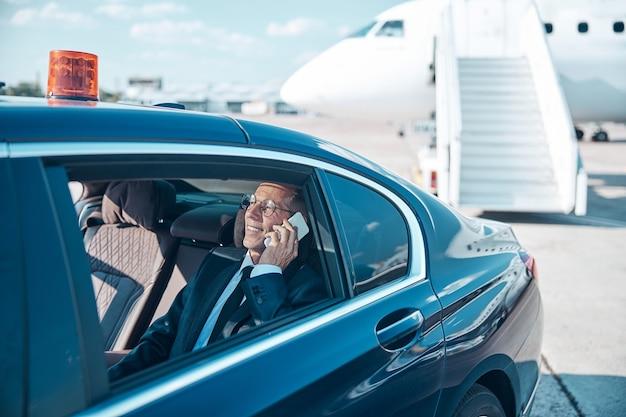 陽気な成熟したビジネスマンは、車の後ろに座って、着陸後に空港を離れる間、携帯電話で話している