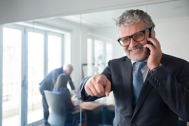 Allegro imprenditore maturo guardando e indicando la fotocamera mentre si è in piedi dalla parete di vetro dell'ufficio, parlando al cellulare e sorridente. copia spazio. comunicazione o concetto di lavoro