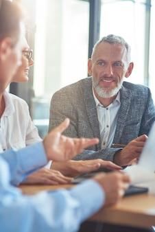 Веселый зрелый бизнесмен сидит с коллегами в современном офисе и что-то обсуждает