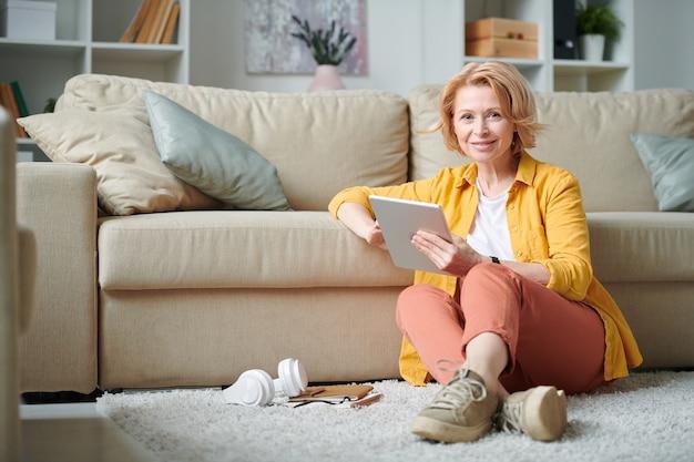 リビングルームのソファに座って、リモートで作業しながらネットでブラウジングカジュアルウェアの陽気な成熟した実業家