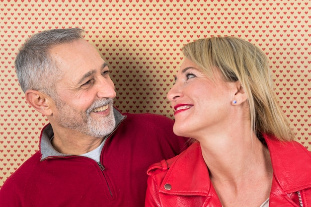 Cheerful mature couple looking at each other against heart shape wallpaper