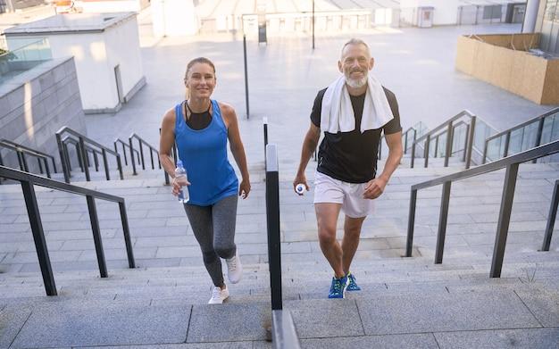 Веселая зрелая пара мужчина и женщина в спортивной одежде, улыбаясь в камеру, поднимаясь по лестнице после