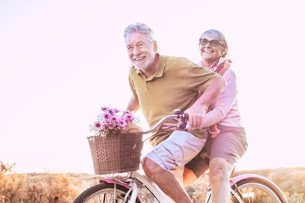 陽気な成熟した先輩のカップルは、自転車に乗ってたくさん笑いながら一緒にアウトドアレジャー活動を楽しんでいます