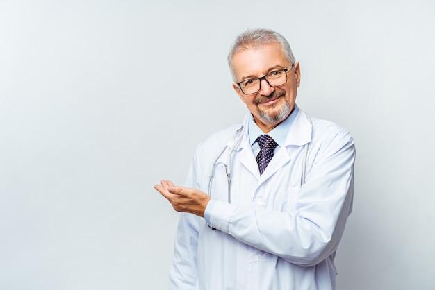 Веселый зрелый доктор позирует и улыбается