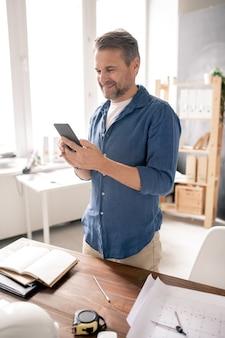 Веселый зрелый инженер со смартфоном просматривает контакты или текстовые сообщения, стоя за столом в офисе