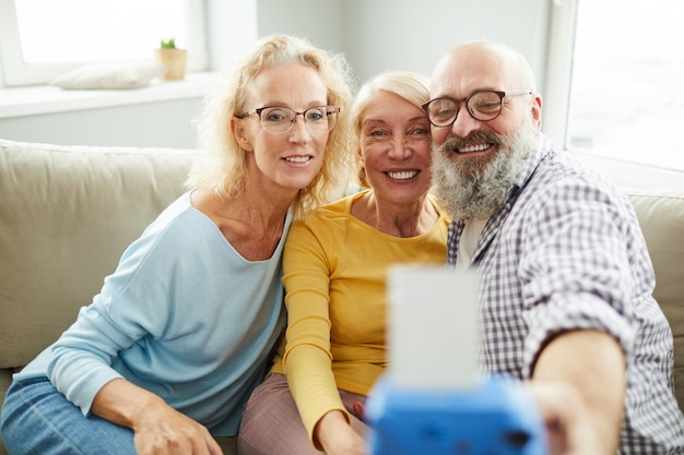 Cheerful mature friends taking photo together