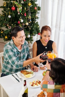 Cheerful mature friends toasting with glasses of wine and juice when celebrating new year at home