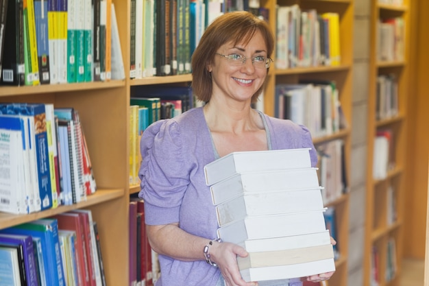 Cheerful mature librarian posing holding a stack of books