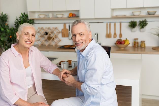 台所に座っている陽気な成熟した愛情のあるカップル家族