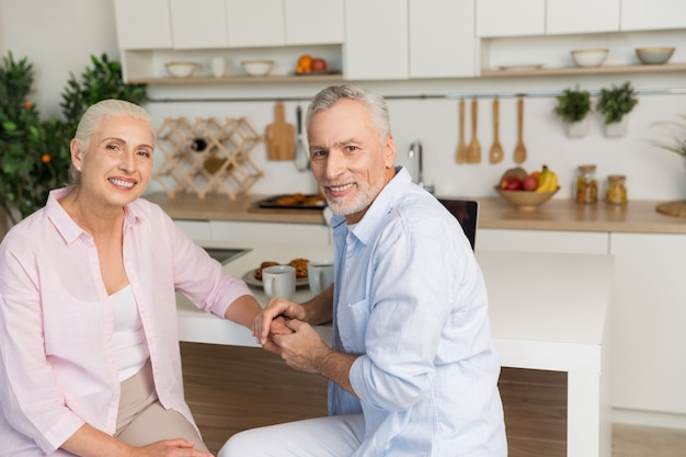 Cheerful mature loving couple family sitting at the kitchen