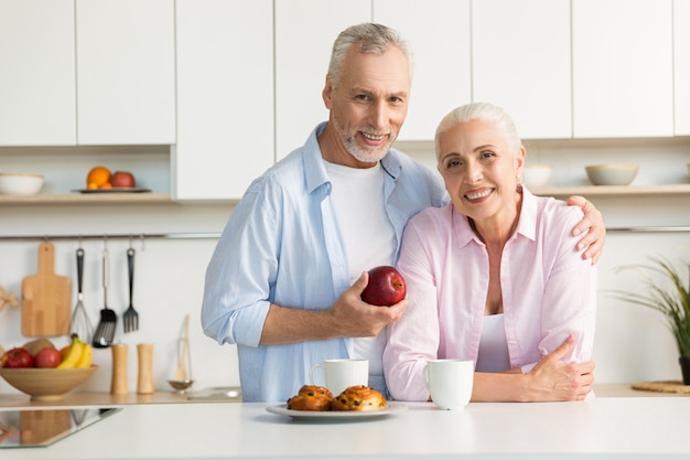 Cheerful mature loving couple family standing at the kitchen.
