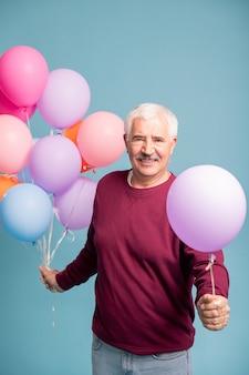 Веселый зрелый мужчина дает вам один воздушный шар из связки, позируя на синей стене