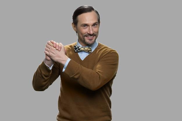그의 손을 함께 잡고 명랑 성숙한 남자입니다. 회색 배경에 카메라 웃는 잘 생긴 남자.