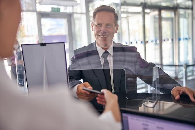 우아한 정장을 입은 쾌활한 성숙한 남자가 책상에 있는 여직원에게 체크인을 위한 문서를 주고 있다