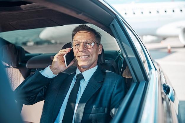 Веселый зрелый мужчина в элегантной одежде общается по мобильному телефону, покидая аэропорт на машине