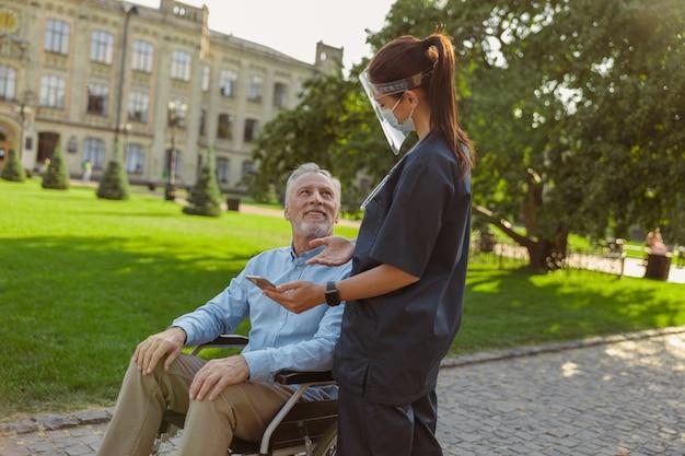 散歩でフェイスシールドとマスクを身に着けている若い看護師に微笑んで車椅子で陽気な成熟した男