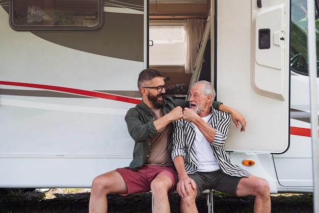 屋外で車のそばに座っている先輩の父と陽気な成熟した男、キャラバンの休日の旅行で楽しい。