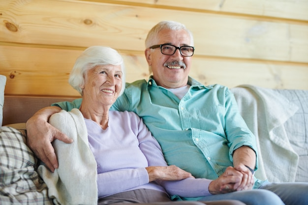 Cheerful mature spouses in casualwear watching program or movie on television while relaxing on couch at home