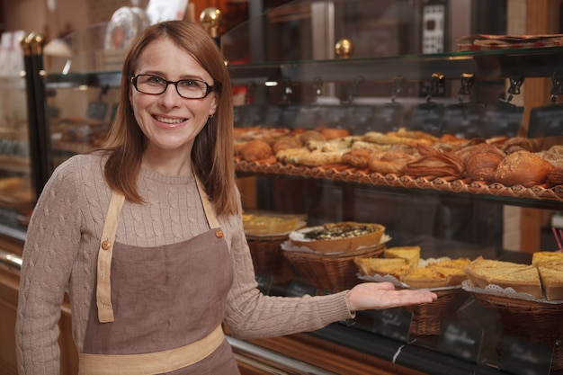 Cheerful mature woman enjoying working at her bakery store, pointing proudly at retail display
