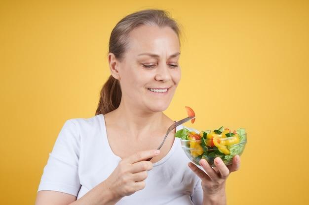 야채 샐러드를 먹는 흰 셔츠에 쾌활 한 성숙한여 인