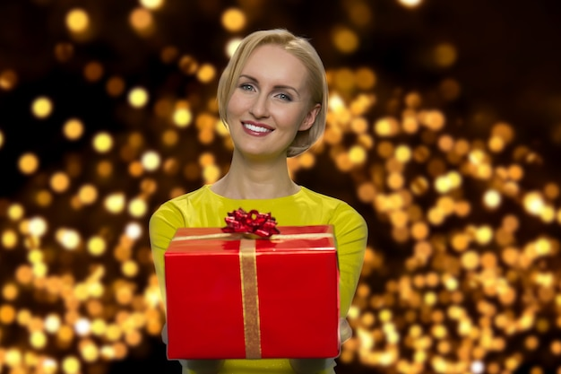 Cheerful mature woman is giving you a present