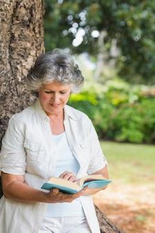 나무 줄기에 기대어 책을 읽고 쾌활 한 성숙한여 인