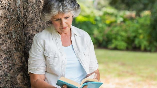 나무 줄기에 앉아 책을 읽고 쾌활 한 성숙한여 인