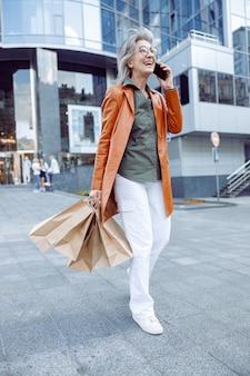 街の通りで携帯電話で買い物をする陽気な成熟した女性