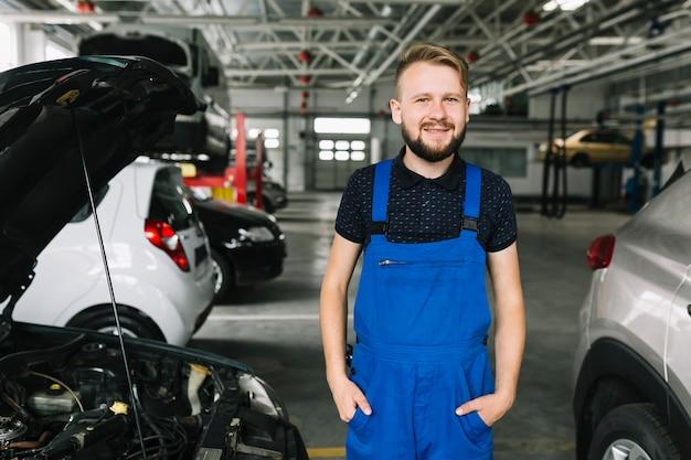 Cheerful mechanic standing near cars