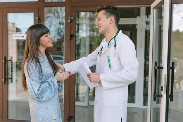 Medico e paziente allegri all'entrata della clinica
