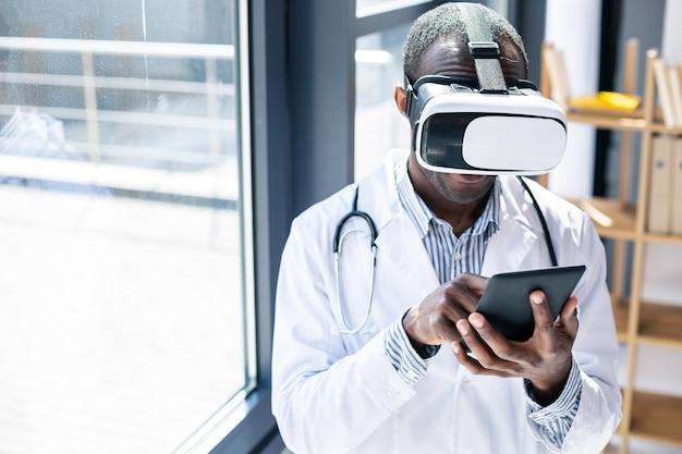 Веселый медицинский работник в маске для виртуального зрения и наслаждается процессом ее использования
