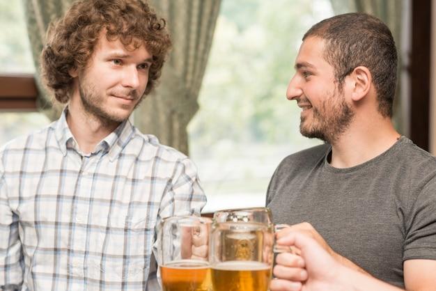Cheerful men clinkingmugs in bar