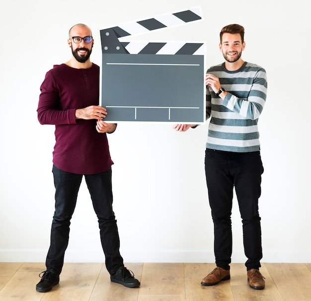 Cheerful men holding clapper board icon