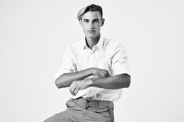 Веселые мужчины в белой рубашке, сидя на стуле, позируют в модном современном стиле