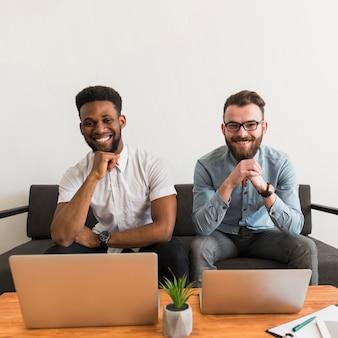 Cheerful men near laptops