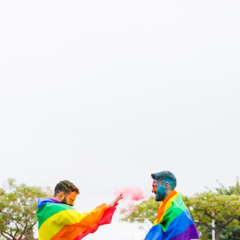 Cheerful men in rainbow flags throwing powder paint on street