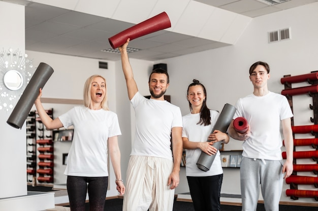 Cheerful men and women are standing with modern gym mats in hands in a fitness studio. group stretching, pilates or yoga training.
