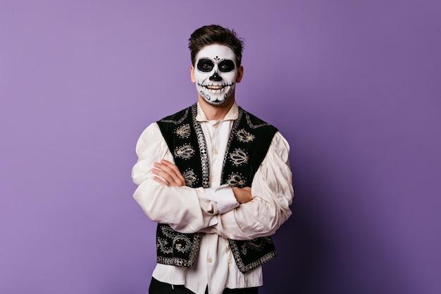 Allegro messicano in abito tradizionale sorride. ritratto di uomo sulla parete lilla.